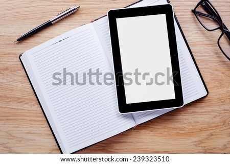 Flower pot, glasses, pen, notebook emphasizing copy space on the tablet screen on light brown desktop - stock photo