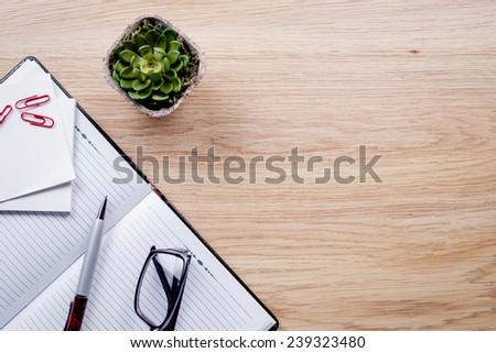 Flower pot, glasses, pen, notebook lie on light brown desktop - stock photo