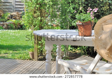 flower pot in a white wooden table with straw hat in garden  - stock photo