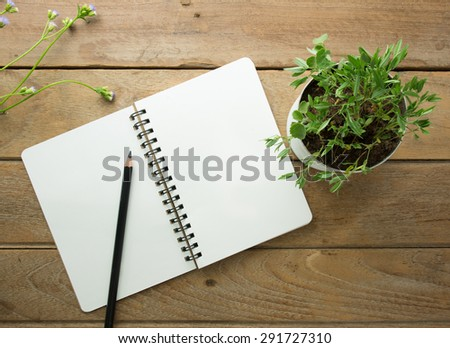 flower pot  Placed on a wood table with notebook and pencil - stock photo