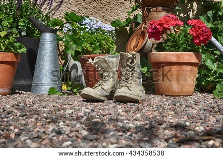 Flower pots and cement boots in a backyard. - stock photo