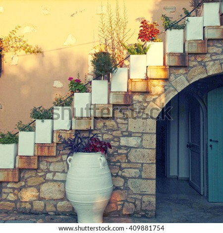 Flower pots on the staircase in old stone house, Crete, Greece. Sunset light, square toned image