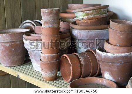 Flower pots; random piles and stacks of vintage flowerpots on wooden shelf - stock photo