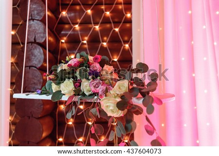 flower rustic arrangement with garland lights on background for wedding reception