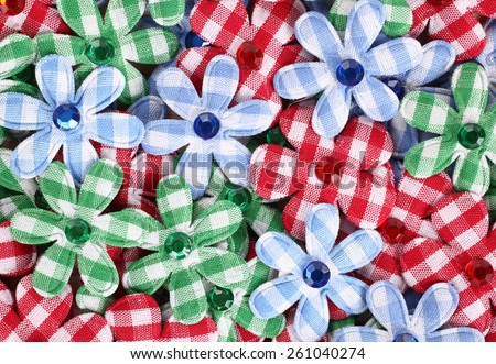 Flower shaped applique pile made of plaid textile - stock photo