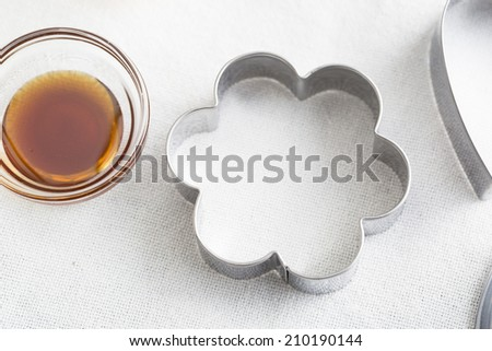 Flower shaped cookie cutter and small glass bowl of vanilla extract. - stock photo