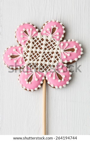 Flower shaped cookie decorated with ornaments on white wooden background. - stock photo