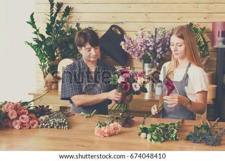 Flower shop, bouquets delivery. Florists, man and woman, creating order from fresh roses.