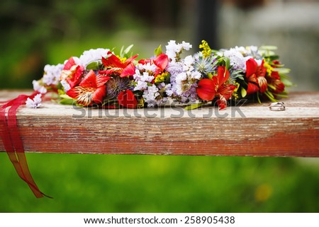 Flower wreath decoration with wedding rings. Selective focus. - stock photo