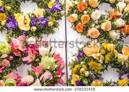 Flower wreaths on white vintage wooden background - stock photo