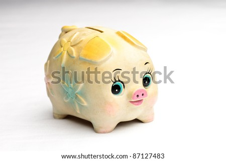 Flowered feminine piggy bank against faded white background