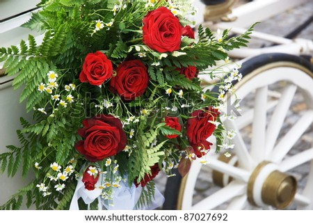 Flowered wedding carriage with huge bouquet on side. The wedding day is one of the most special days in life. Focus on flowers, wheel defocused - stock photo