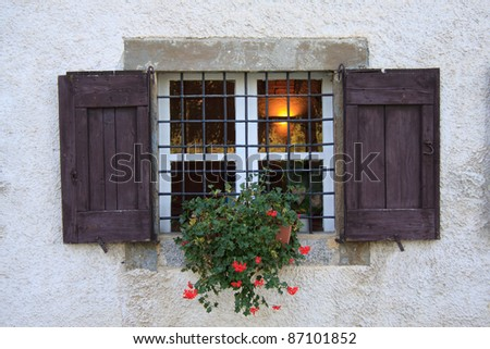 flowered windowsill in old farmhouse of Lombardy - stock photo