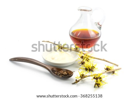 flowering witch hazel (Hamamelis), dried leaves, cream and essence for homemade skin care cosmetics and bath additive, isolated with shadow on a white background - stock photo