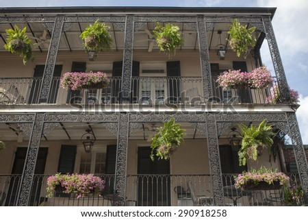 Flowerpots hanging from the balcony with exquisite ironwork at the French Quarter, New Orleans, Louisiana  - stock photo