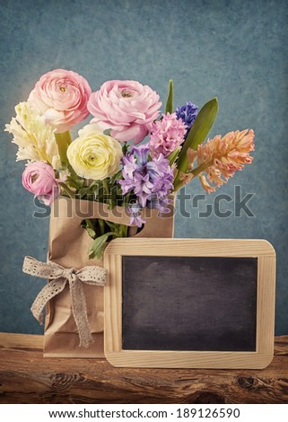 Flowers and a black chalk board - stock photo
