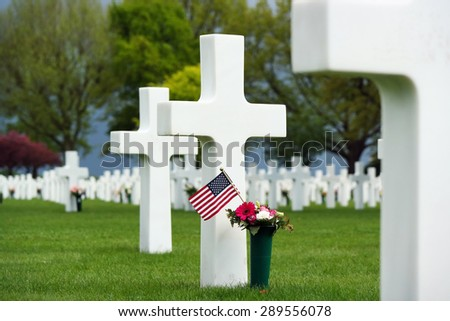 Flowers and a small flag of the US between cross headstones at the American military cemetery in Margraten, The Netherlands. - stock photo
