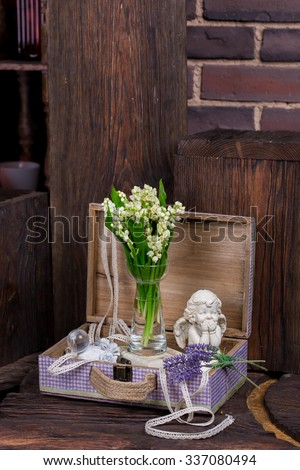 Flowers and angel decor composition. Lily of the Valley and lavender flovers, and angel figure jn the brown wood table - stock photo