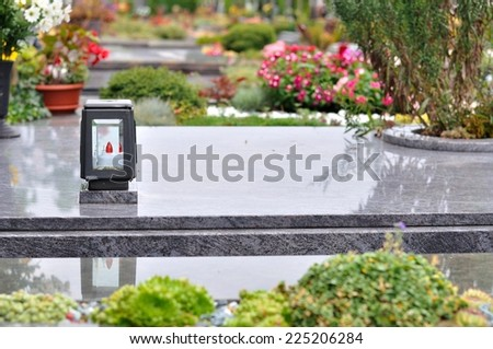 Flowers and candle on tomb in churchyard - stock photo