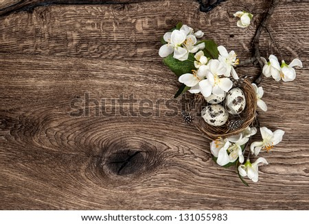 flowers and easter nest with eggs on rustic wooden background. spring apple tree blossom