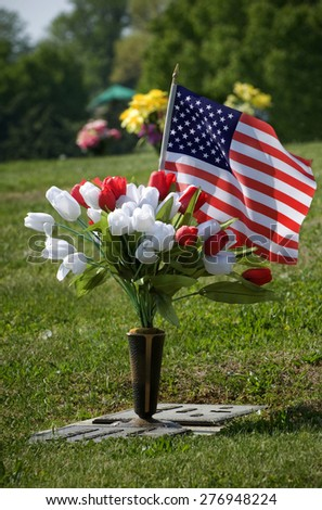 Flowers and flag for a fallen soldier/ Casualty Of War Fallen Soldier  - stock photo