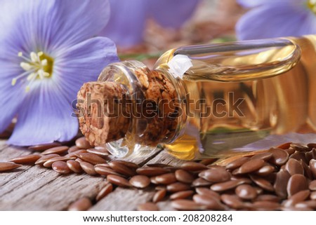 flowers and flax seed, oil in glass bottle macro on wooden background horizontal  - stock photo
