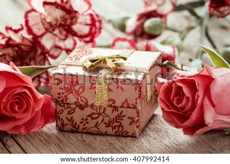 Flowers and gift box on a wooden background - stock photo