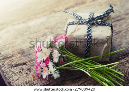 Flowers and present gift on wooden background/ Holiday background - stock photo