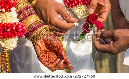 Flowers and silk is split between the groom and priests hands next to the henna covered hand of the bride during the vowels part of a South Indian wedding ritual   - stock photo