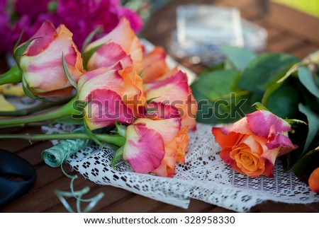 flowers and tools on the table, florist workplace, still life top view - stock photo