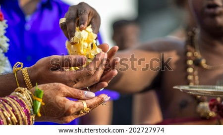 Flowers are handed from the Hindu priest to the wedding couple during a south Indian wedding - stock photo