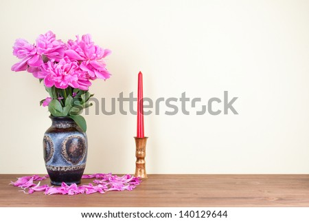 Flowers bouquet in vintage vase and candle on wooden table