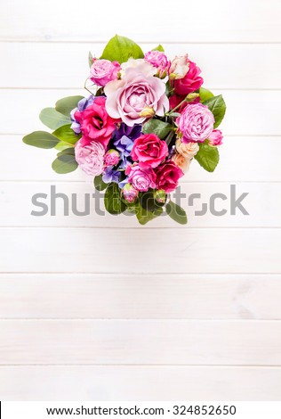 flowers. bouquet of roses in a bucket on a white wooden background - stock photo