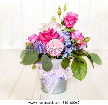 flowers. bouquet of roses in a bucket on a white wooden background