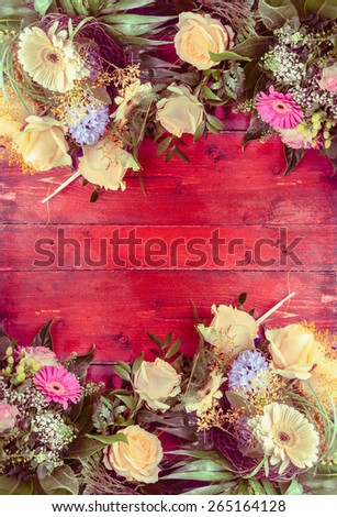 Flowers bunch on red wooden background, top view, frame with place for text - stock photo