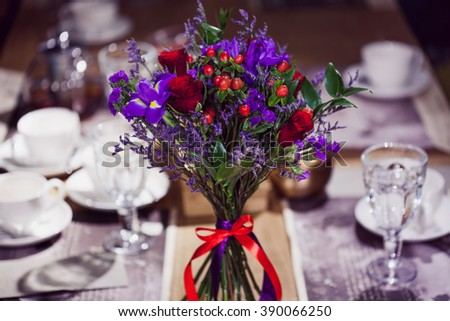 Flowers composition in restaurant, small red roses and purple irises, combination of multiple colors
