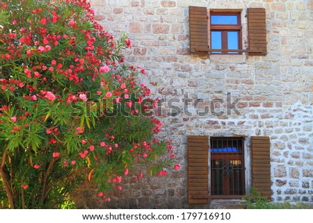 Flowers cover the facade of stone building in old Mediterranean town - stock photo