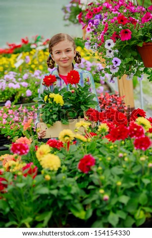 Flowers for garden - Lovely girl holding flowers in garden center - stock photo