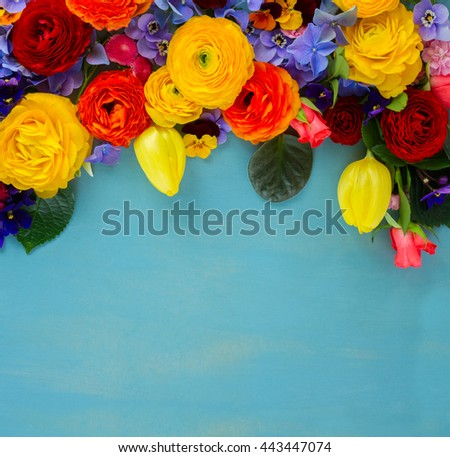 Flowers fresh festive border composition on blue table background with copy space - stock photo