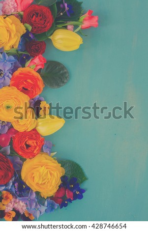 Flowers fresh festive border composition on blue wooden table, retro toned - stock photo
