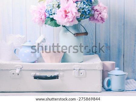 Flowers in a blue vintage can on white retro bag and kitchen earthenware - stock photo