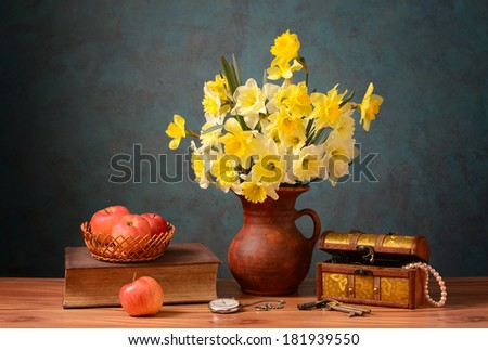Flowers in a ceramic vase and apples on the table - stock photo