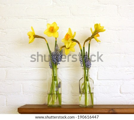 flowers in a glass bottle standing on a shelf against a white stone wall
