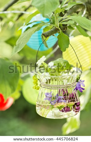 flowers in a glass with water hanging in a tree in the garden