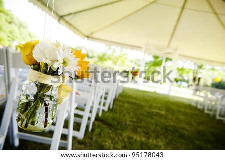 flowers in a mason jar at a wedding ceremony - stock photo