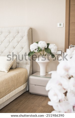flowers in a vase on the nightstand in the bedroom - stock photo