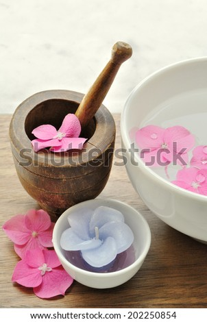 Flowers in a water bowl with a candle and a wooden pestle for ar