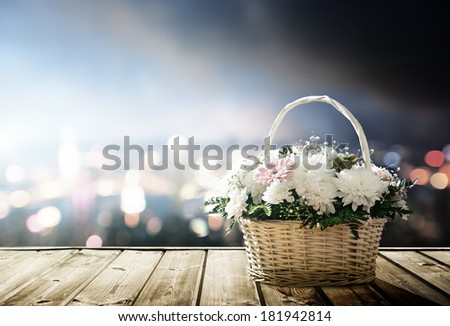 flowers in basket and lights of night city - stock photo