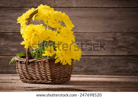 flowers in basket on wooden background - stock photo