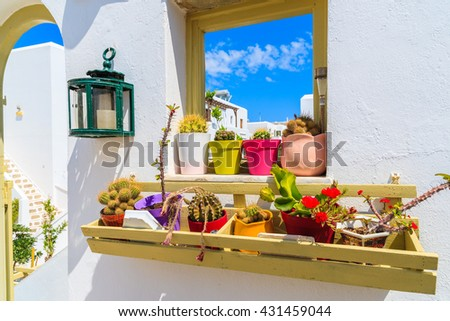 Flowers in pots on window sill in beautiful Naoussa village, Paros island, Cyclades, Greece - stock photo